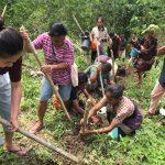 pria dan wanita turut serta membawa gulungan pipa dan menggali tanah untuk instalasi saluran air